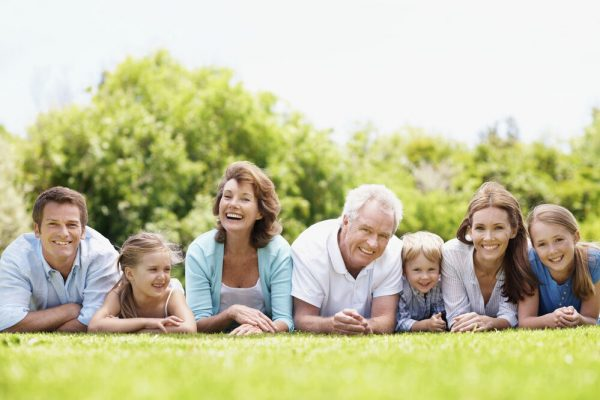 Smiling and happy family lying together on the grass outdoors